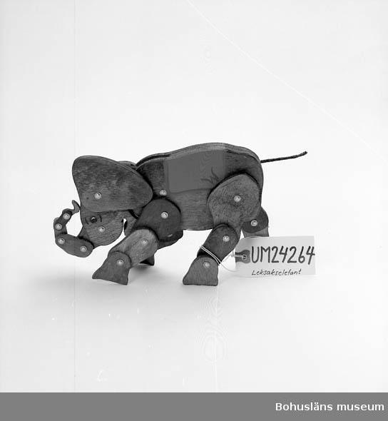 """571 Användningstid *OANVÄND  Leksakselefant med ledade ben och ledad snabel. Gråbetsad, med målat öga och målat grönt """"ryggtäcke"""" med röd kant märkt med W.  Elefanten hör samman med UM15924 - UM15925. Delarna bildar tillsammans """"Cirkus Wengse"""". Utanpå kartong till UM15924 och UM15925 finns tryckt bild på delarna, bl a denna elefant. Insamlad från leksaksaffären Leksakshörnan, i samband med att man samlade in rivningsmaterial till basutställningen från den byggnad där affären legat. Det var affärsinnehavaren som skänkte den.  För mer uppgifter om butiken: Se UM15810.  Omkatalogiserat 1999-06-04 VBT"""