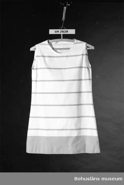 Grön och vitrandig. Ärmlös. Brukaren var givarnas dotter. Hon var född 1953.  Till klänningen använde hon gröna stövlar med snörning.