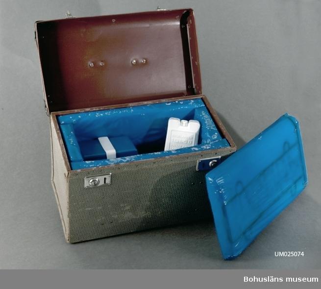 """Före detta konduktörsväska omgjord till frysväska av givaren. Klädd med frigolit i blå plast på insidan. 6 st bitar. I den ena biten är det hål. Väskan är svart och vit och beige rutig. Bärhandtag. Innehåll: 2 st. vita frysklampar med lock, text: """"EPA SPORT KYLKLAMPEN IGLOO HÅLLER KALLT LÄNGRE FÖRVARA KLAMPEN I KYLSKÅPETS FRYSFACK ELLER I FRYSSKÅPET DEN ÄR DÅ ALLTID KLAR ATT ANVÄNDAS. NÄR KYLVÄSKAN ELLER BOXEN PACKATS LÄGG I EN ELLER TVÅ KLAMPAR. TILLVERKAD AV REIS-FABRIKEN A.-B. FORSHAGA"""", 2 st gula äggfodral (6 ägg i varje), 1 st plastbehållare, blå, för smör och margarin, 1 st plastbehållare, beige och grön för smör och margarin."""