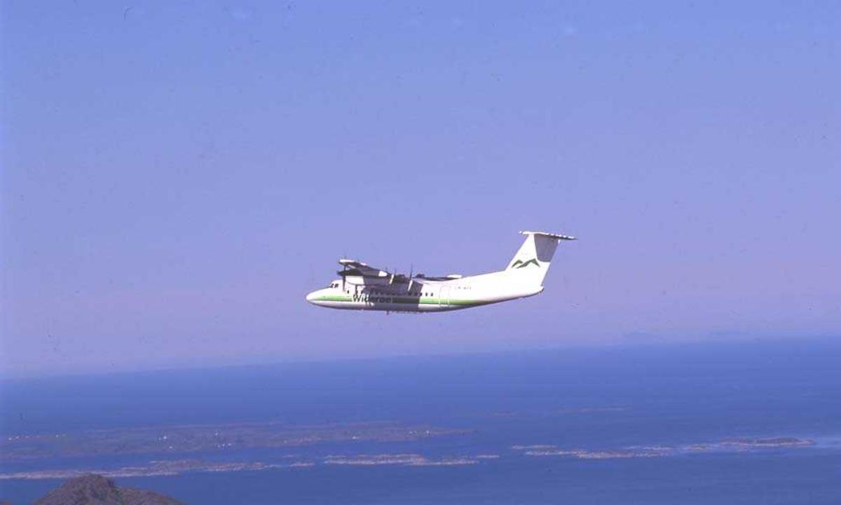 Luftfoto. Ett fly, LN-WFK, DHC-7-102 / Dash7 fra Widerøe.  Øyene som vi ser er Helligvær nord for Bodø og i bakgrunnen skimtes Vest-Lofoten.