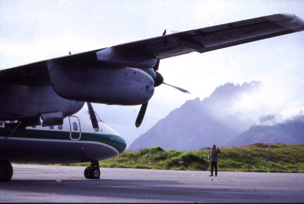 Lufthavn/flyplass.Svolvær/Helle. Et fly, DHC-7-102 Dash7 fra Widerøe klar for oppstart ved hjelp av lufthavnbetjent (marshall)