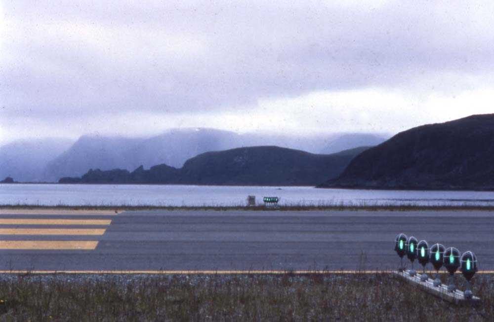Lufthavn. Honningsvåg. Foran på bildet krysser rullebanen og i bakgrunnen Kamøyfjorden og Selvågklubben.