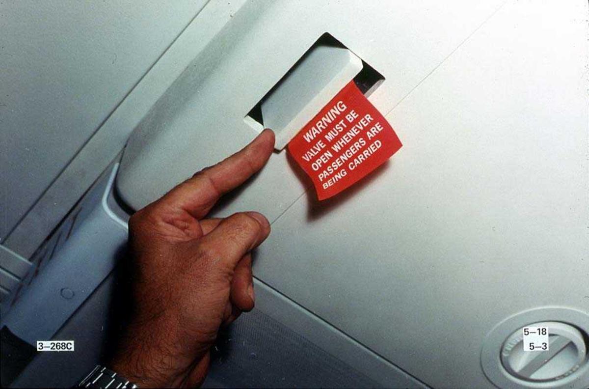 En person som peker på en luke hvor det henger en merkelapp på, inne i en Boeing 737-200.