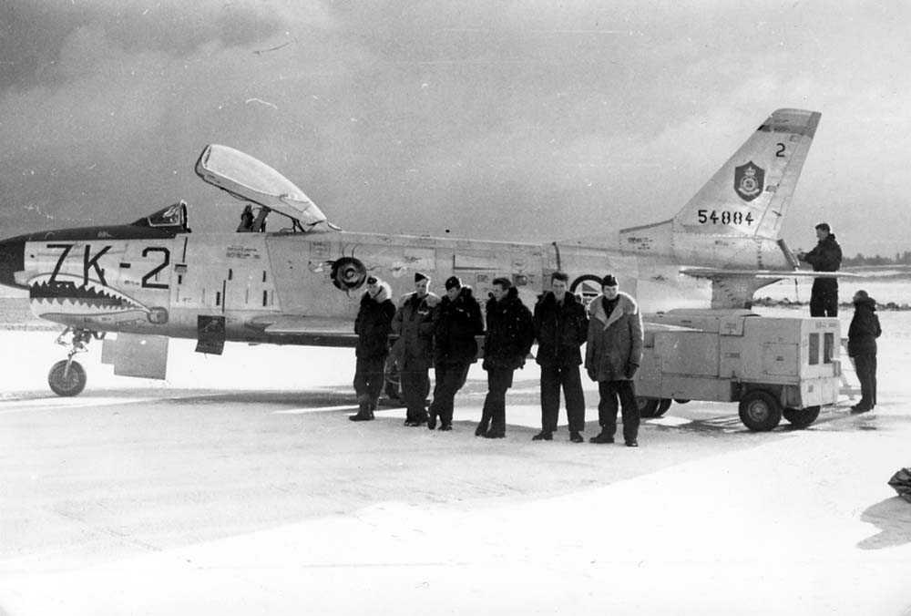 Lufthavn. Ett fly på bakken. Seks personer står foran flyet, to personer står bak ved motoren på flyet. F-86K