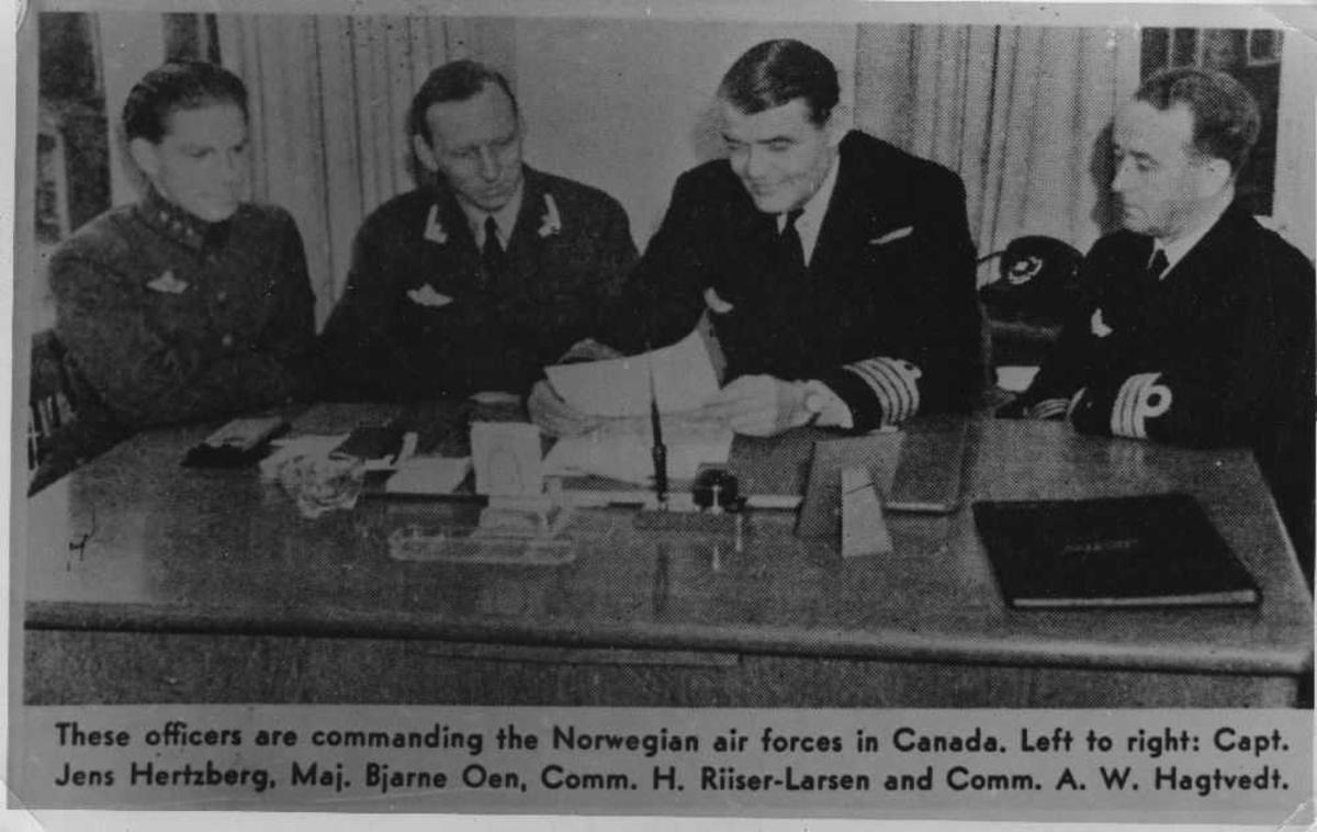 Kontor. Ved et bord sitter 4 personer, offiserer, fra det Norske Luftforsvaret (Norwegian air forces in Canada). Teksten på bildet forteller oss hvem de er.