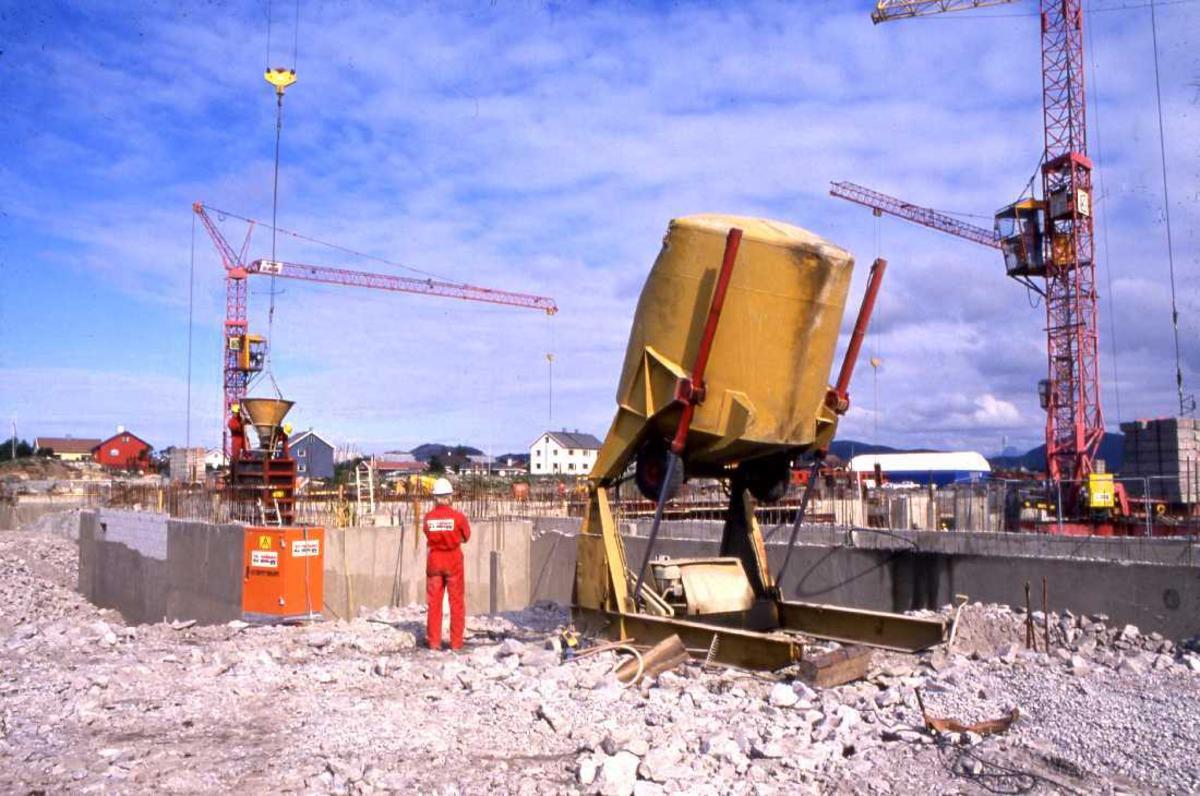 Lufthavn - flyplass. Grunnarbeidet er godt igang på byggetomta og anleggsmaskiner i virksomhet. En person overvåker arbeidet.