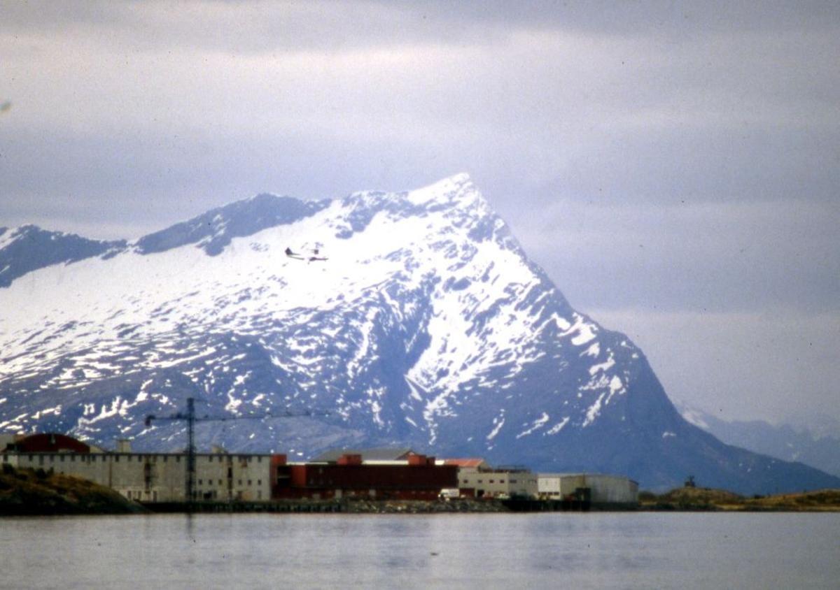 Landskap. Et fly, DHC-7-102 Dash 7 fra Widerøe. Under innflyging til Bodø bane 08 (runway). I bakgrunn Sandhornet (Sandhornøy, Gildeskål).