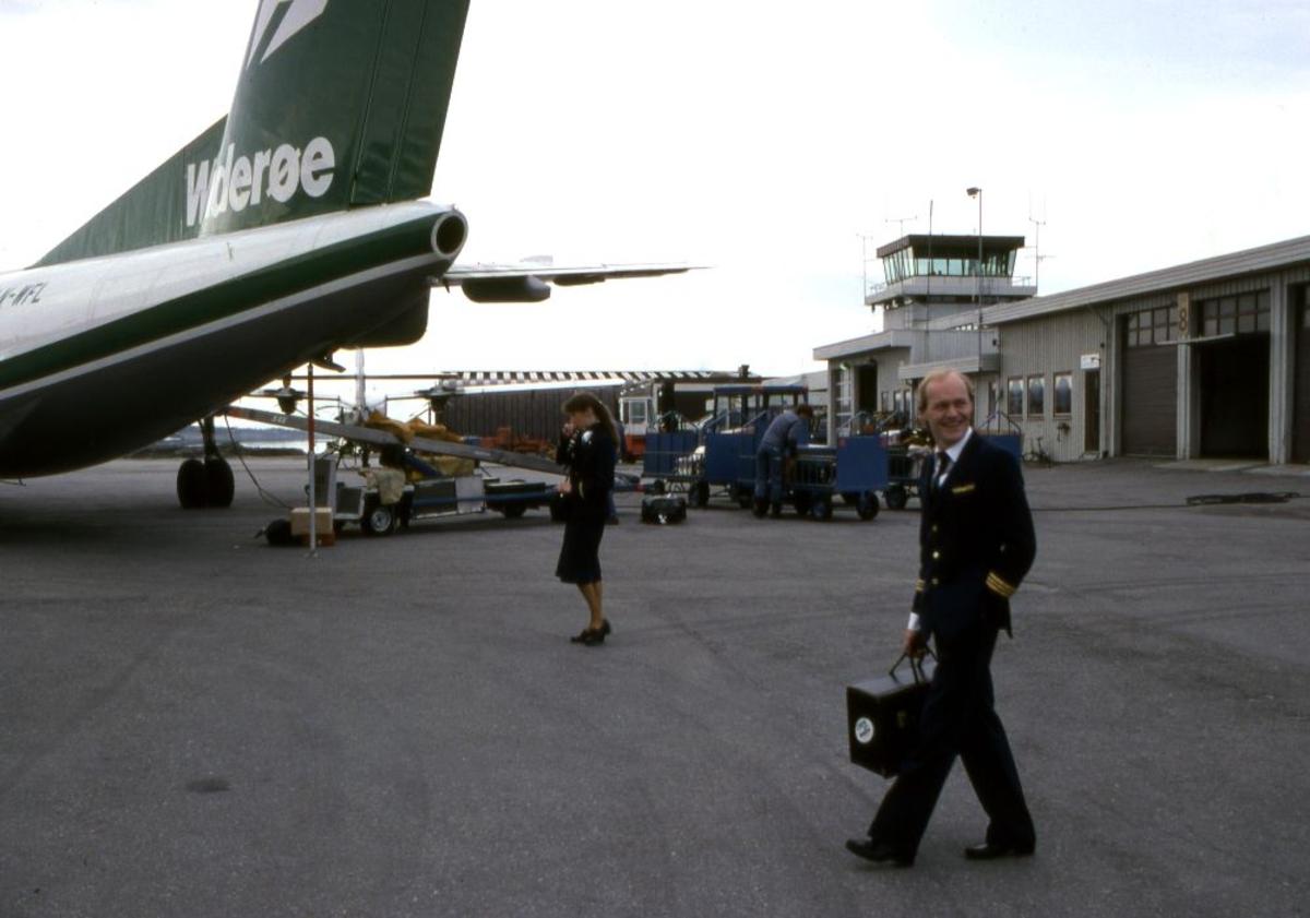 Lufthavn (flyplass). Halepartiet på et fly, LN-WFL, DHC-7-102 Dash 7 fra Widerøe. To personer, pilot (flyger) og kabinansatt underveis til flyet. I bakgrunn Flytårnet.