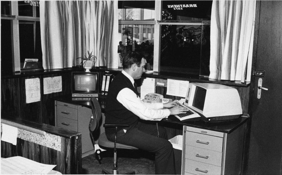 """Landskap (kontor). Braathens SAFE Informasjon, Fornebu, """"Lost & Found"""".  En person skriver på en datamaskin."""