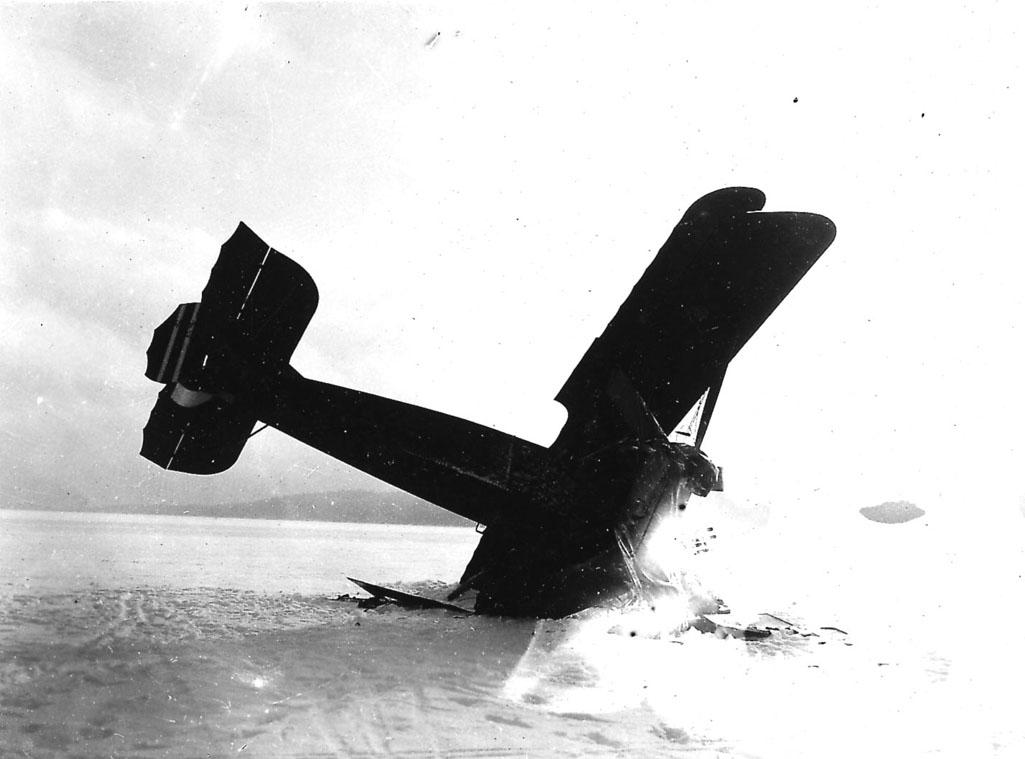 Åpen plass, ett fly, havarert Kaje, med framenden og ene vingespissen ned i bakken. Snø.