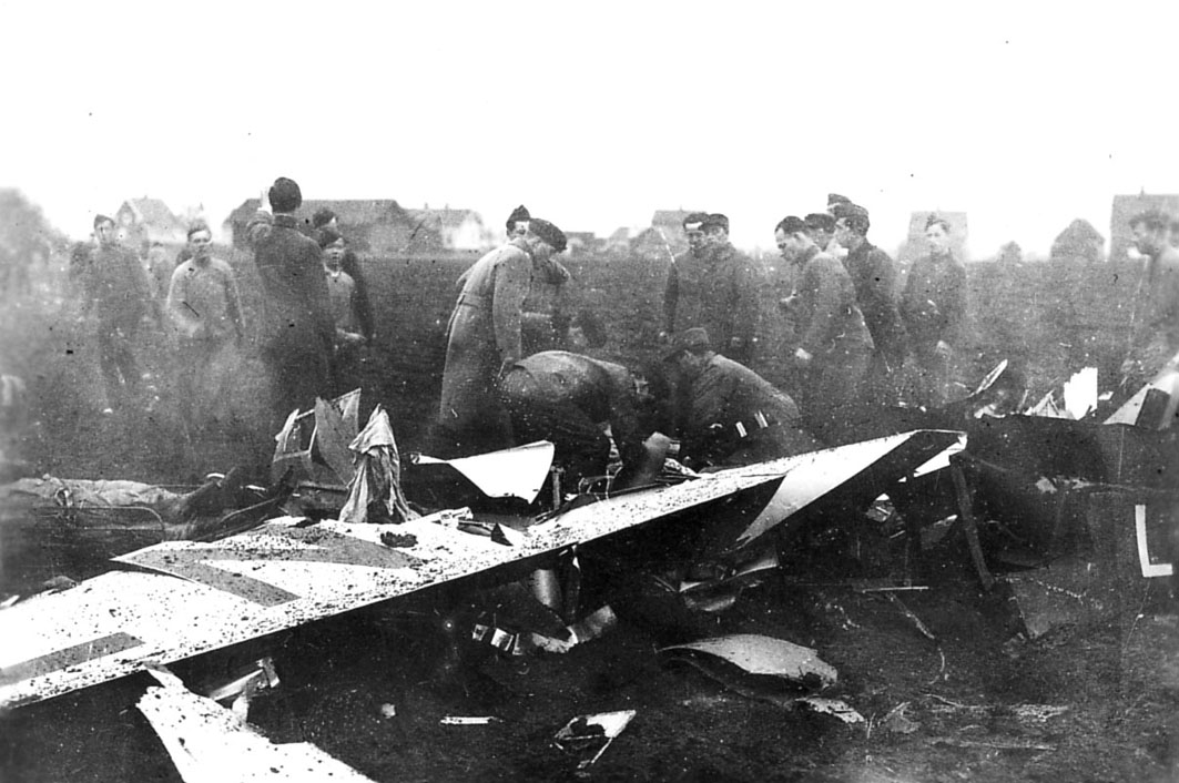 Åpen plass.Kjeller  Flystyrt, havari, ett flyvrak ligger på bakken. Noen personer, soldater, ved vraket. En person ligger på båre i venstre billedkant. helt