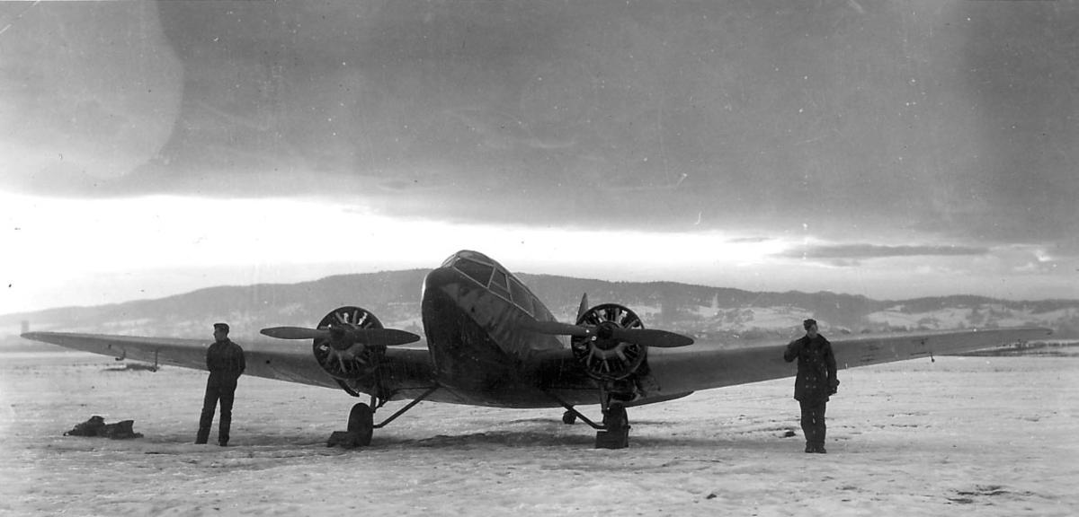 """Åpen plass, ant. lufthavn. ett fly på bakken. Airspeed """"Envoy""""  to personer, soldater, foran flyet."""