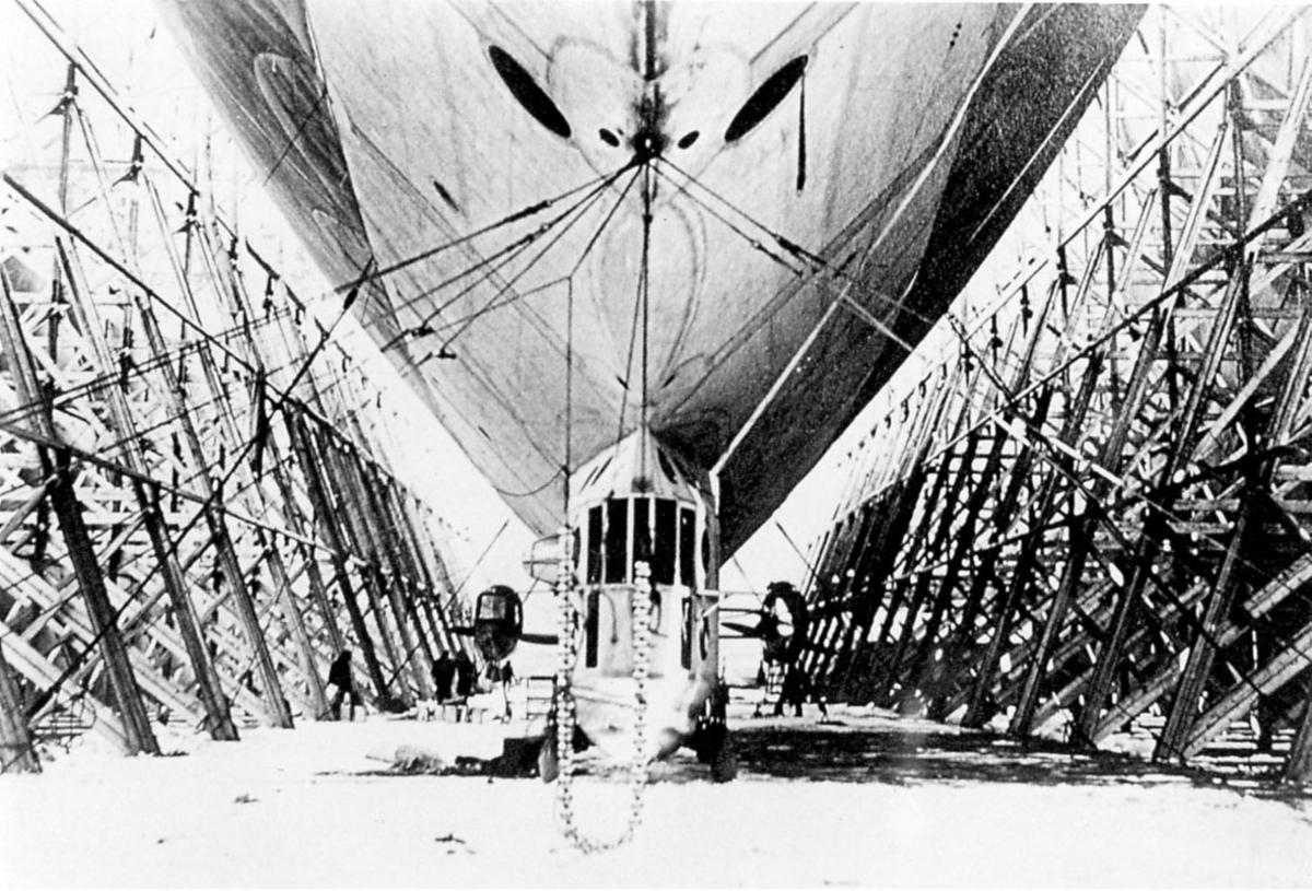 """Ett luftskip,"""" Italia """" Står på bakken festet med """"barduner"""" inne i luftskiphangar. Åpne """"vegger"""" på begge sider. Antagelig Svalbard."""
