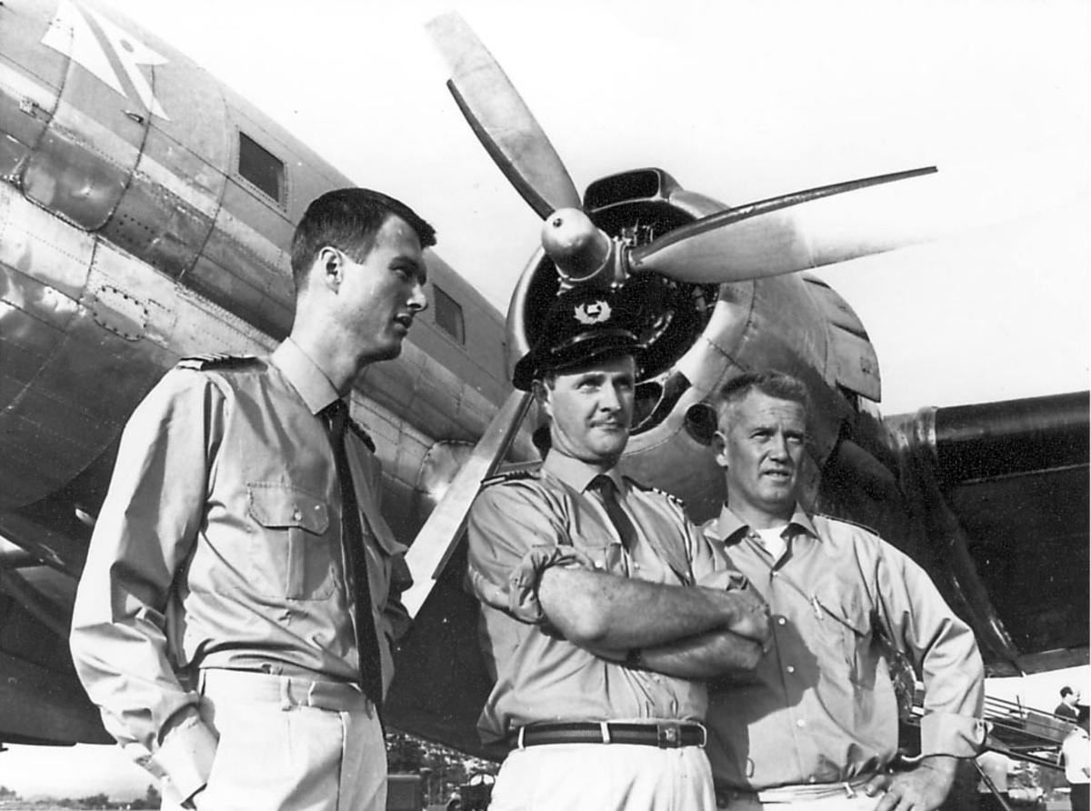 Tre personer, flygere, står ved siden av ett fly.