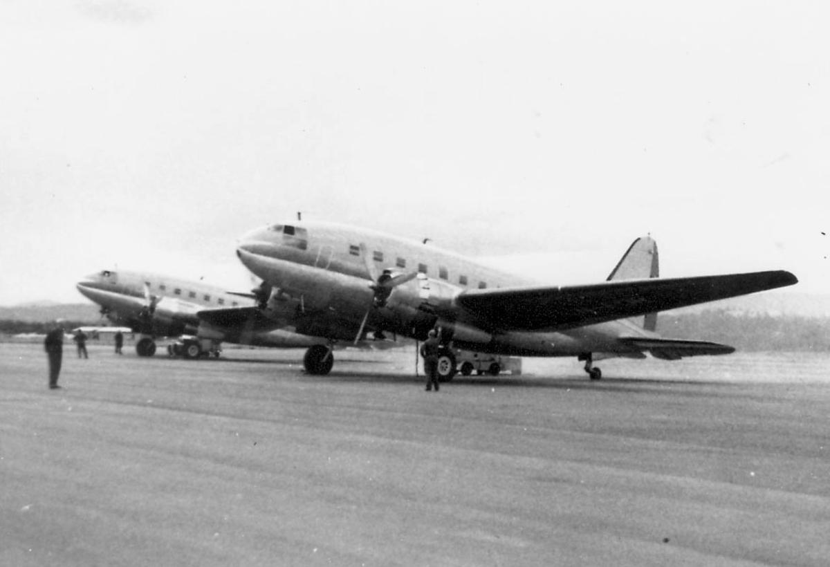 Åpen plass, lufthavn. to av de tre Curtis C-46R på bakken