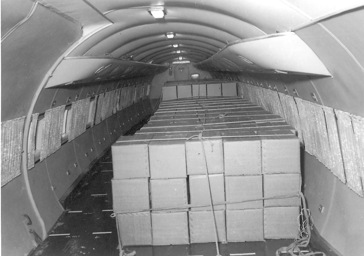 Flyinteriør, cabin uten seter. Stabel med kartonger. (Lasterom?)