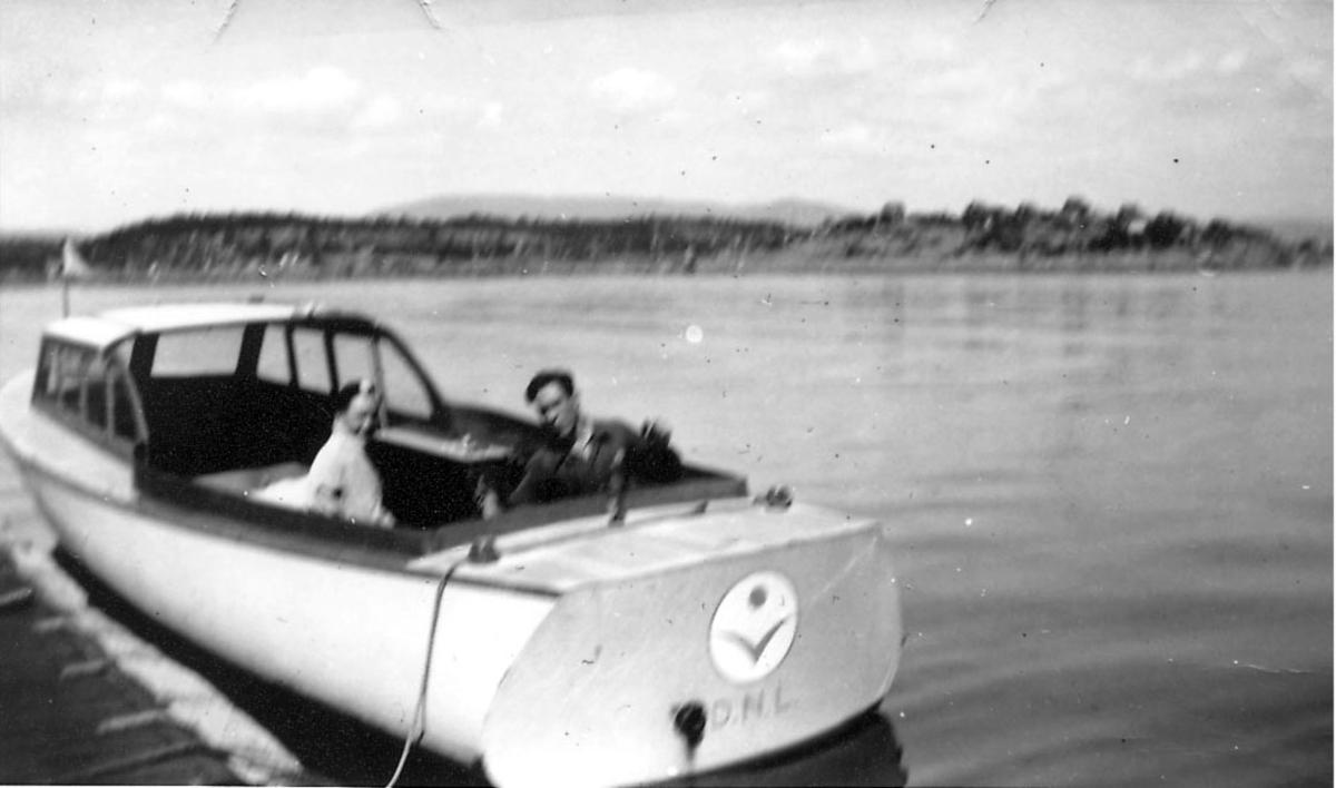 En liten båt, tilbringerbåt, merket med DNL og logo. to personer ombord. Ant. fra sjøflyhavn.