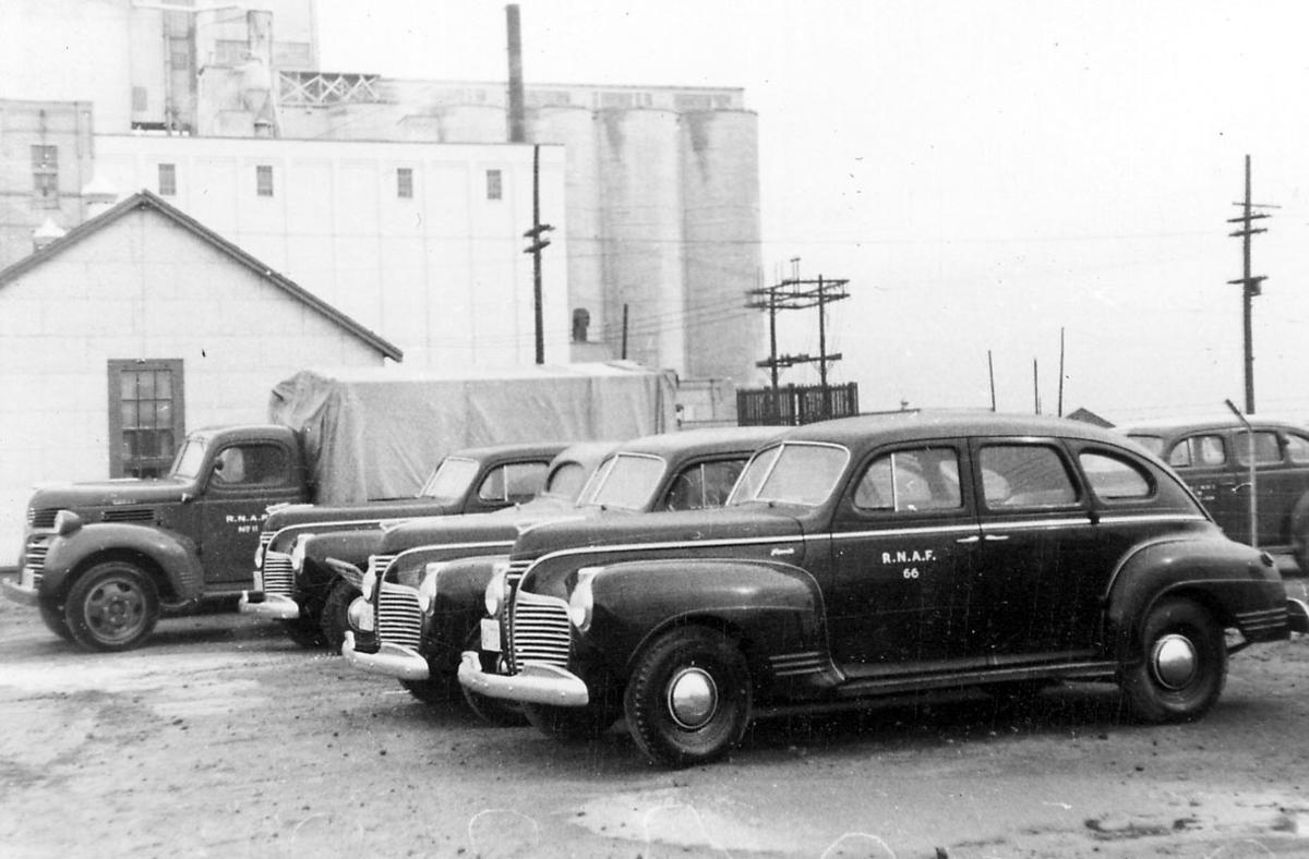 Flere biler som tilhører R.N.A.F. Større bygning i bakgrunnen