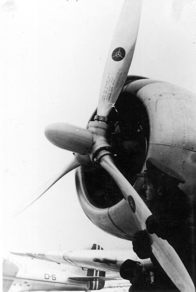 Portrett, to personer i militæruniform, ved et fly. En av dem holder i et av propellbladene. Annet fly bak, merket D-5.