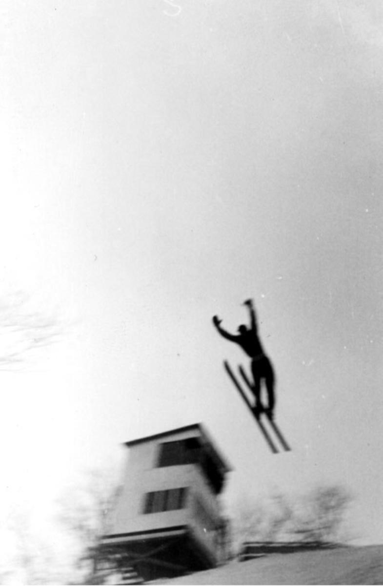 Portrett, en person i hoppbakken under selve svevet.