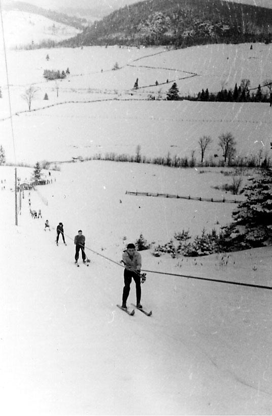 Snødekt skråning, flere personer på ski blir trukket oppover av skitrekk.