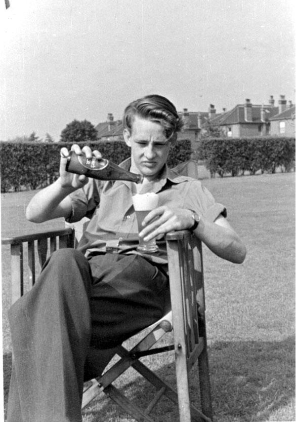 Portrett, en person, militær, sitter utendørs i en klappstol med ølflaske og glass.