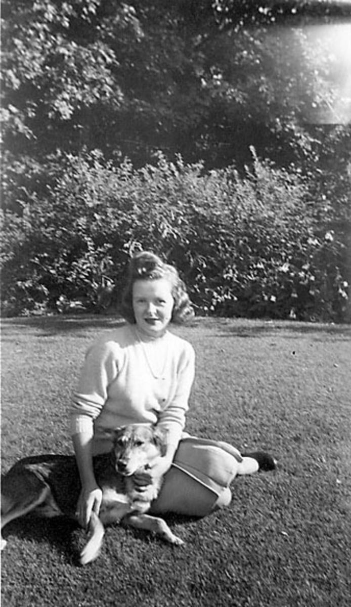Portrett, person sitter på bakken, ant. i en park, og leker med en hund. Ung kvinne i sivile klær.