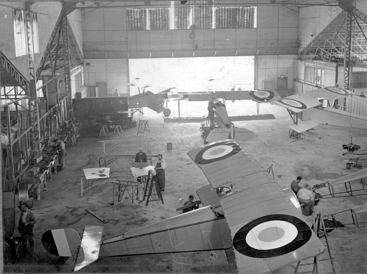 Fly, 4 stk. Nieuport 11C.1, inne i hangar. Sett ovenfra. Flere personer arbeider med flyene.