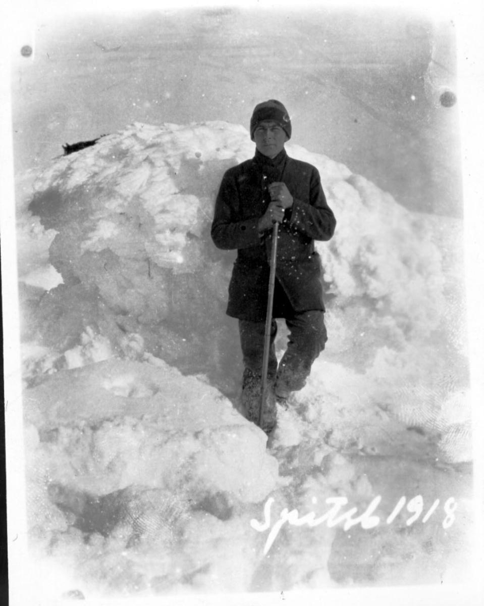 1 person foran snøhaug, med spade e.l. i hendene.