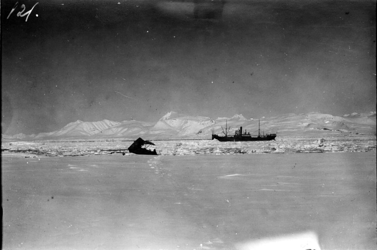 """Deler av et fly ved strandkanten, iskanten. Fartøy/båt bak, D/S """"Chantier"""" losser. Snø på bakken, fjell i bakgrunnen."""