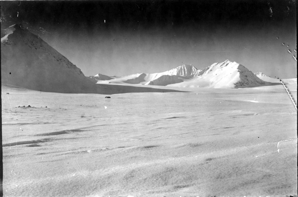 Landskap fra Svalbard. Åpen snødekt flate foran, mindre fjell bak.