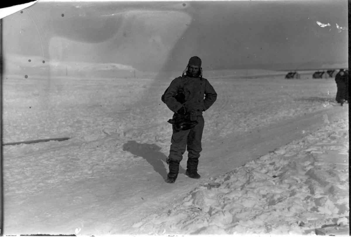 """1 person på """"vei"""", i forgrunnen, flyger fra Svalbard. Andre personer bak t.h. Noen bygninger bak. Snø på bakken."""