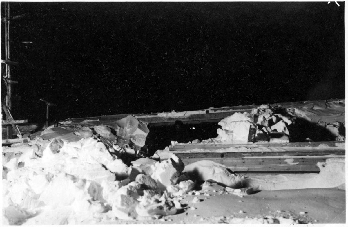 Matrialer til luftskipshangaren ligger nedsnødd. En person holder på med å måke e.l.