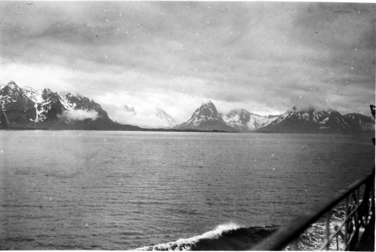 Havet i forgrunnen, fjell i bakgrunnen, Nord-Norsk landskap. Tatt fra fartøy - båt, litt av rekka sees.