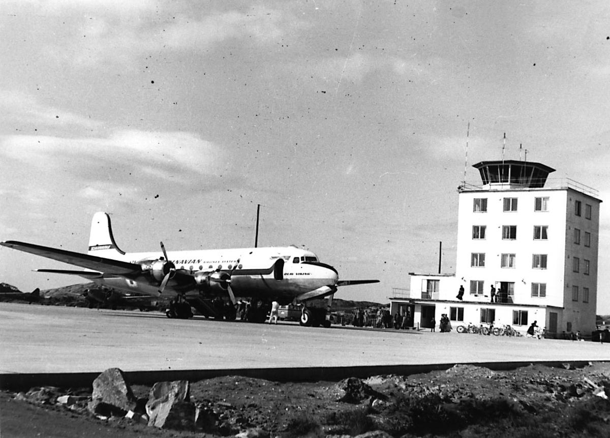 """Lufthavn, 1 fly på bakken, DC-4 """"Olav Viking"""" fra SAS, Kontrolltårnet bak."""