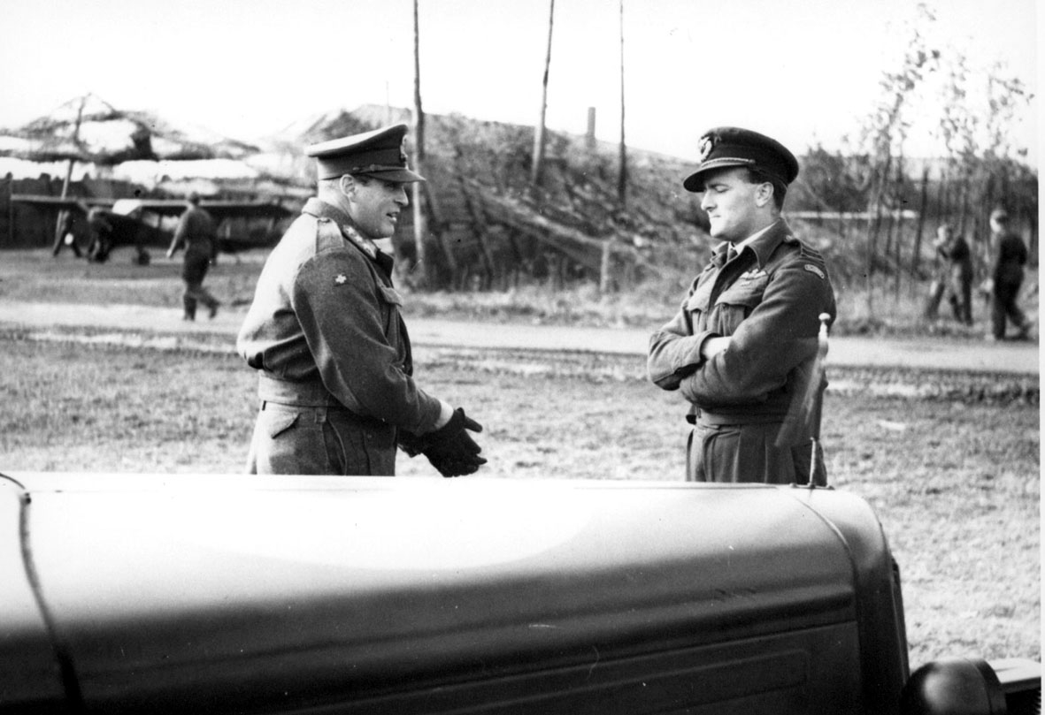 2 personer i militæruniform. Kronprins Olav i samtale med offiser. Fronten på en bil i forgrunnen. Noen personer, soldater og bygninger i bakgrunnen.