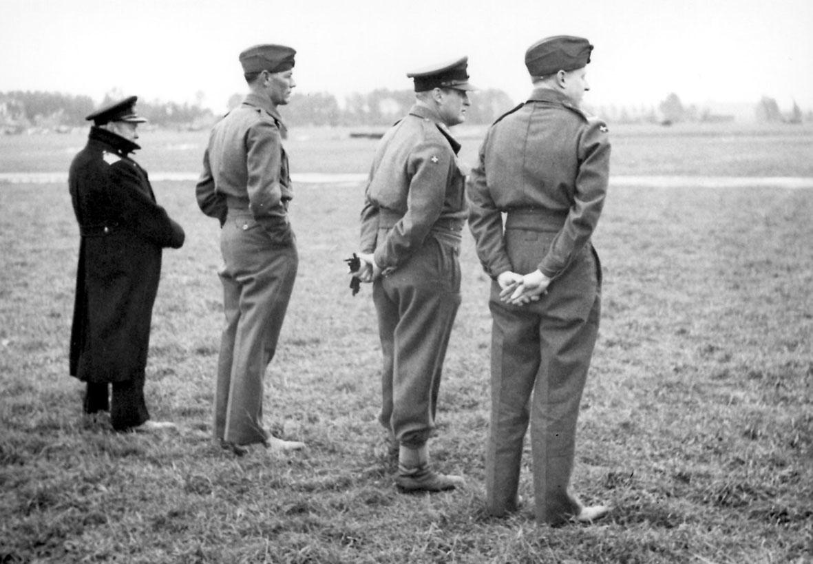 4 personer i militæruniform. Kronprins Olav og 3 andre, på en åpen plass.
