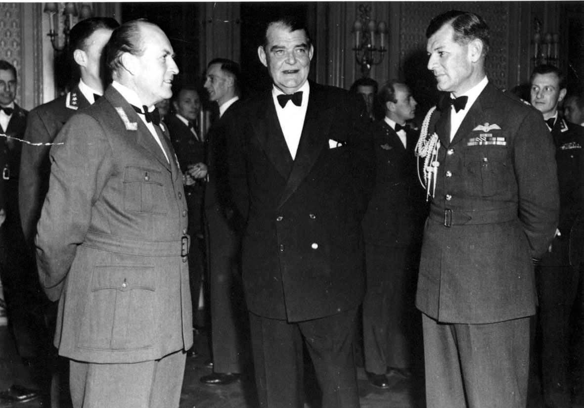 Flere personer, i militæruniform, tatt innendørs. Kronprins Olav foran t.h.