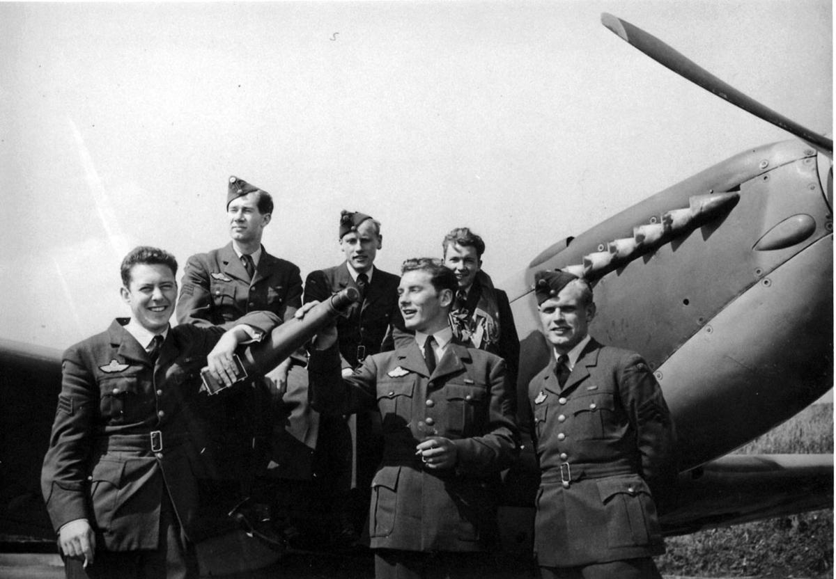 6 personer i militæruniform foran fly, Spitfire.
