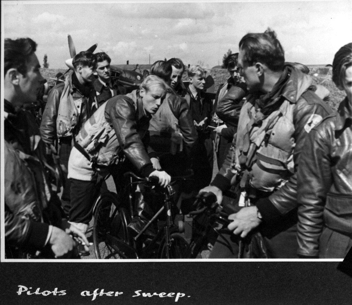 Flere personer i militæruniform - pilotutstyr. Litt av fly bak, Spitfire. Engelsk håndskrevet tekst under bildet.