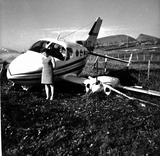 """Fly, Cessna 401A, LN-TVX. Skrått forfra. """"Ligger"""" ute på et jorde. Ene vingen nede i bakken. 1 person står foran flyet."""