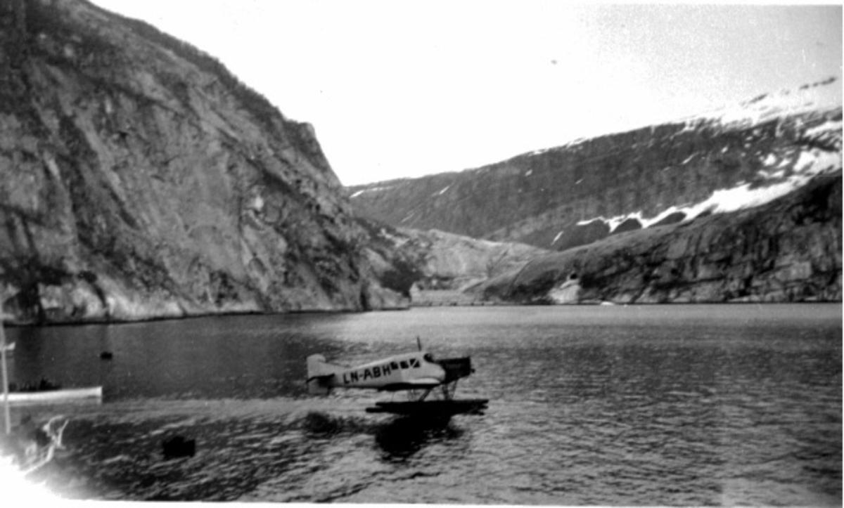 Fly i sakte fart på havoverflata. Junkers F13W, LN-ABH. Fra siden. Åpen båt med flere personer i venstre billedkant.