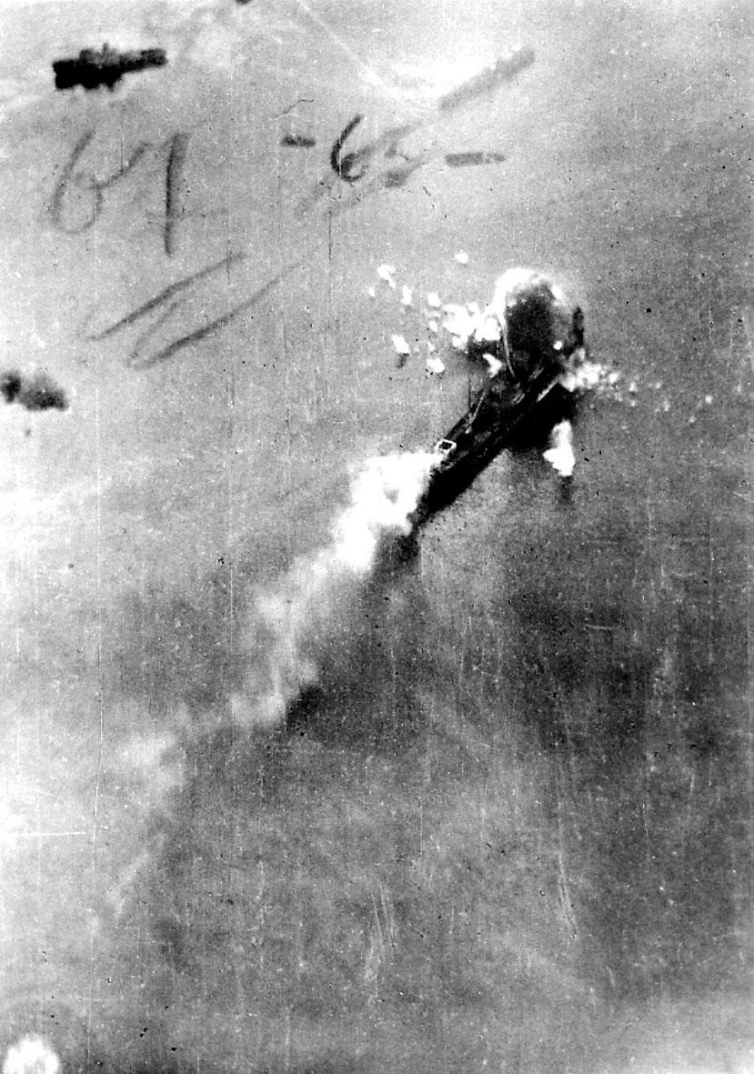 Luftfoto. Fartøy i brann etter bombeangrep. Røyk stiger til værs.