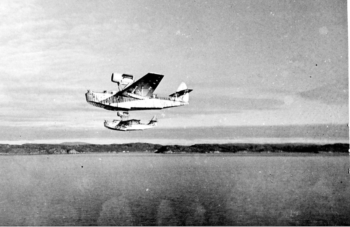 Luftfoto. 2 fly, MBR-2s like over havoverflata, sett fra siden. Nnoen bygninger inne på land i bakgrunnen.