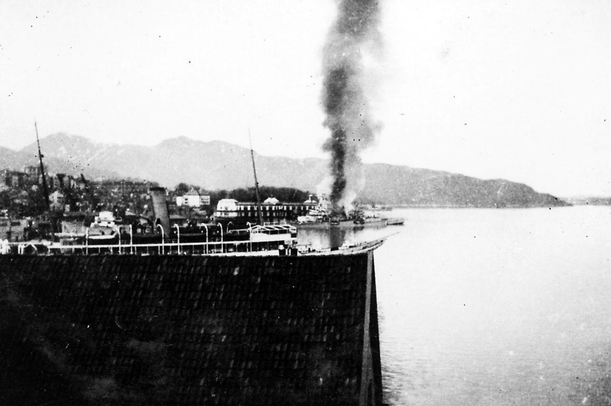 Havneområde. Bak seees et militærfartøy hvor det stiger røyk opp fra fartøyet.
