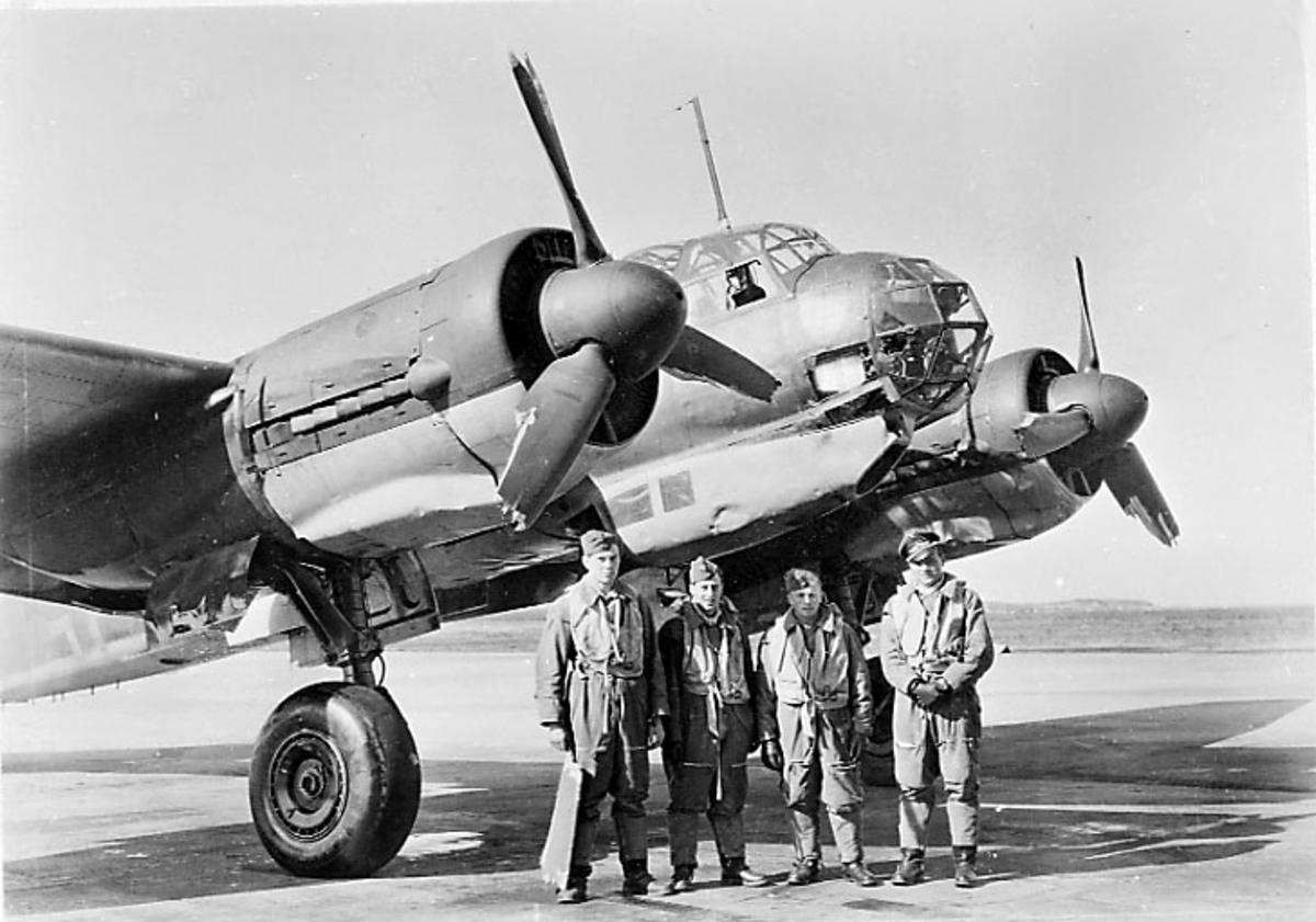1 fly, Junkers JU-88 A eller D . Står på bakken, forparten sett skrått forfra. 4 personer, militære, i pilotutstyr, står ved flyet.