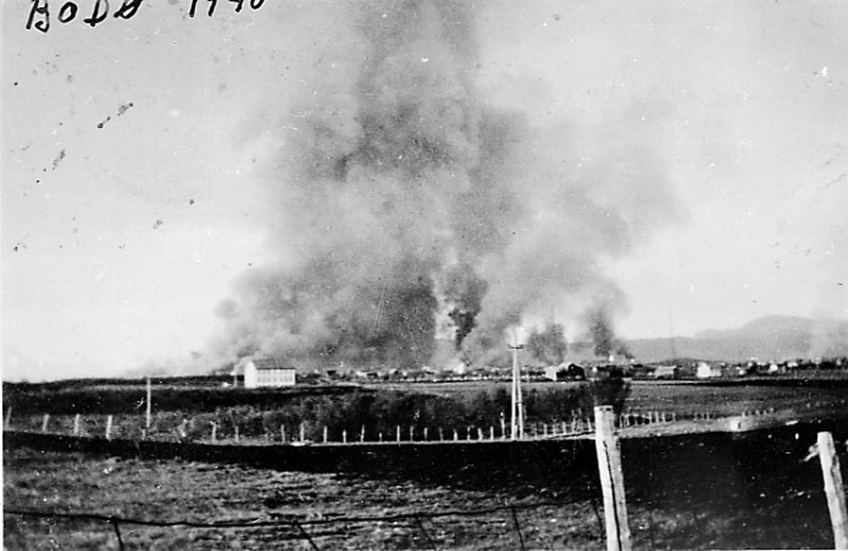 Bodø i brann etter bombingen under 2. verdenskrig, sett fra Hernes. Jorder i forgrunnen.