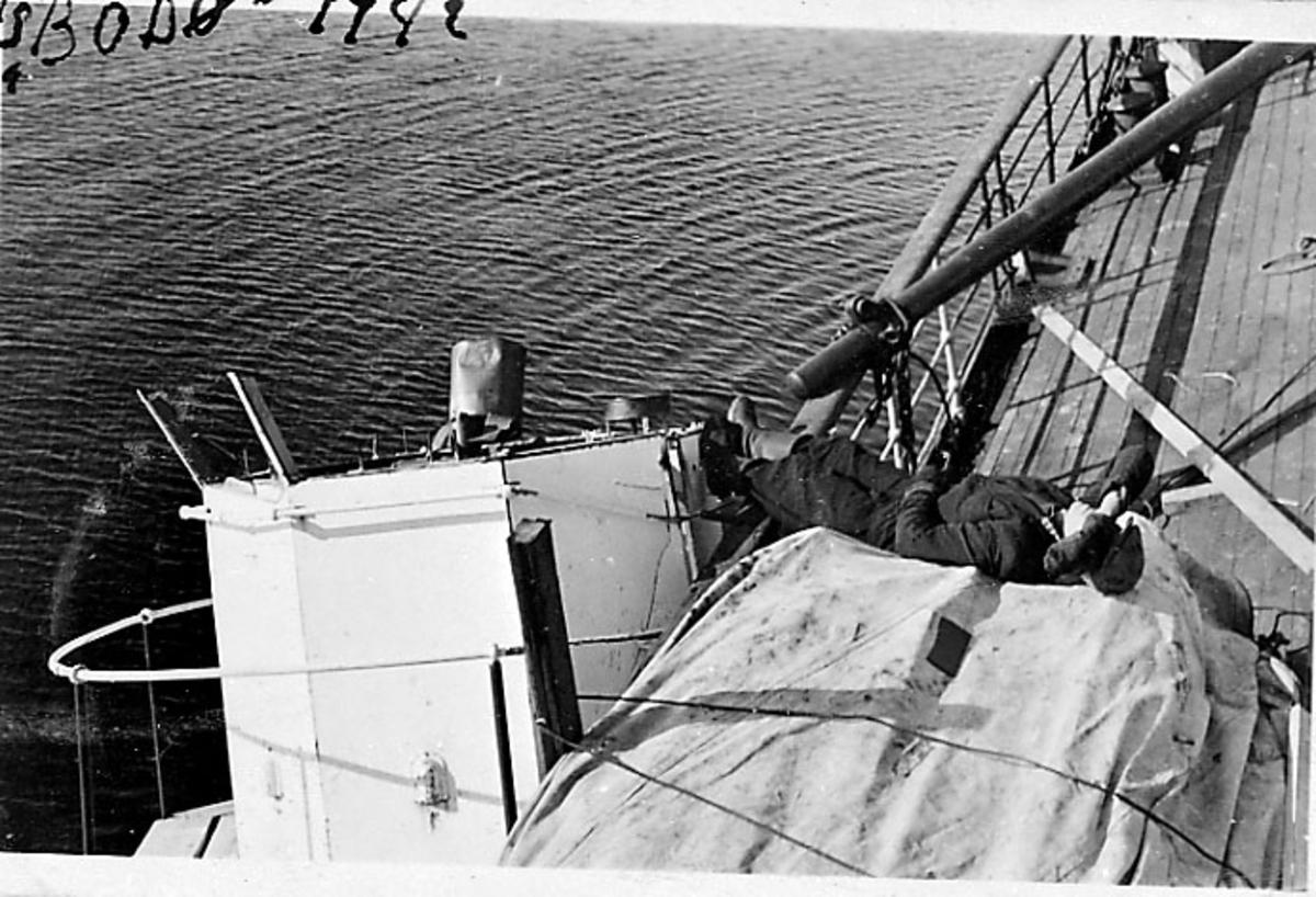 """Fartøy på grunn ved sjømerke, D/S Bodø, ombord i fartøyet. 1 person """"slapper av"""" på dekk."""