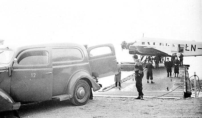 Sjøflyhavn, 1 fly, Junkers ligger ved flytebrygge. Flere personer og kjøretøy, Ford V8 1937 varebil.
