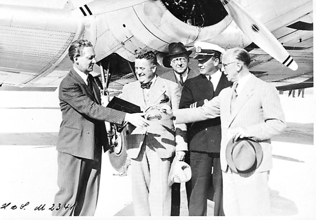 """Lufthavn, 1 fly på bakken. Fokker F.XII SE-ACZ """"Varmland"""" fra Swedish AB Aerotransport. Litt av ene motoren. 5 personer foran motoren, en av dem i flyuniform."""